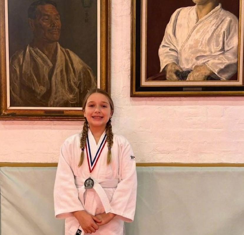 小七在柔道比赛中获得银牌,戴着两条辫子看起来很可爱
